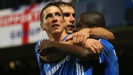 Fernando Torres is mobbed by team-mates after his late winner.