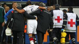 Sami Khedira is helped off the field after colliding with Italy's Andrea Pirlo.