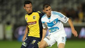 John Hutchinson of the Mariners contests the ball with James Troisi of the Victory.