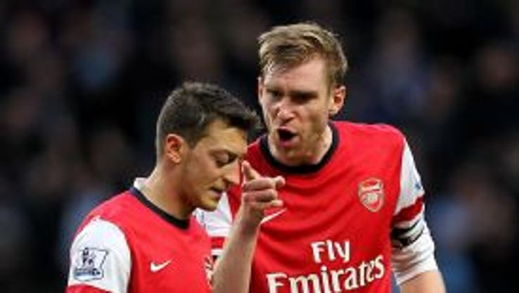 Mesut Ozil receives a telling off from Per Mertesacker after the loss at City.