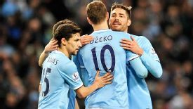 Edin Dzeko is mobbed after giving Man City the lead against Palace.