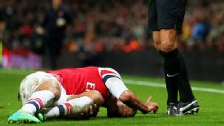 Theo Walcott holds his knee in agony.