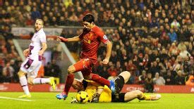 Luis Suarez goes down under a challenge from Brad Guzan to give Liverpool a penalty -- and the chance to earn a point.