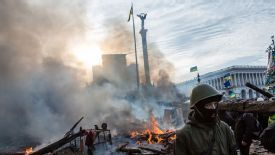 Anti-government protesters walk amid debris and flames near the perimeter of Independence Square, known as Maidan, on Feb. 19, 2014 in Kiev, Ukraine.