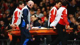 Hat trick hero Robin van Persie is stretchered off at the end of the victory over Olympiakos.