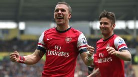 Lukas Podolski celebrates scoring Arsenal's third away at Hull.