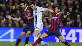 Sergio Busquets and Javier Mascherano of Barcelona tackle Edin Dzeko of Manchester City.
