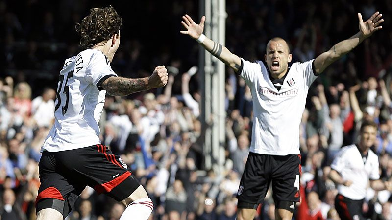 Fernando Amorebieta celebrates with John Heitinga after scoring Fulham's second.