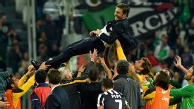 Jubilant Juventus players lift coach Antonio Conte at the end of last night's victory.
