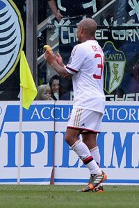 Nigel de Jong picks up a banana thrown from the stands during the defeat to Atalanta.