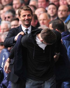 Tim Sherwood lets a fan take his seat in the dugout during Tottenham's victory.