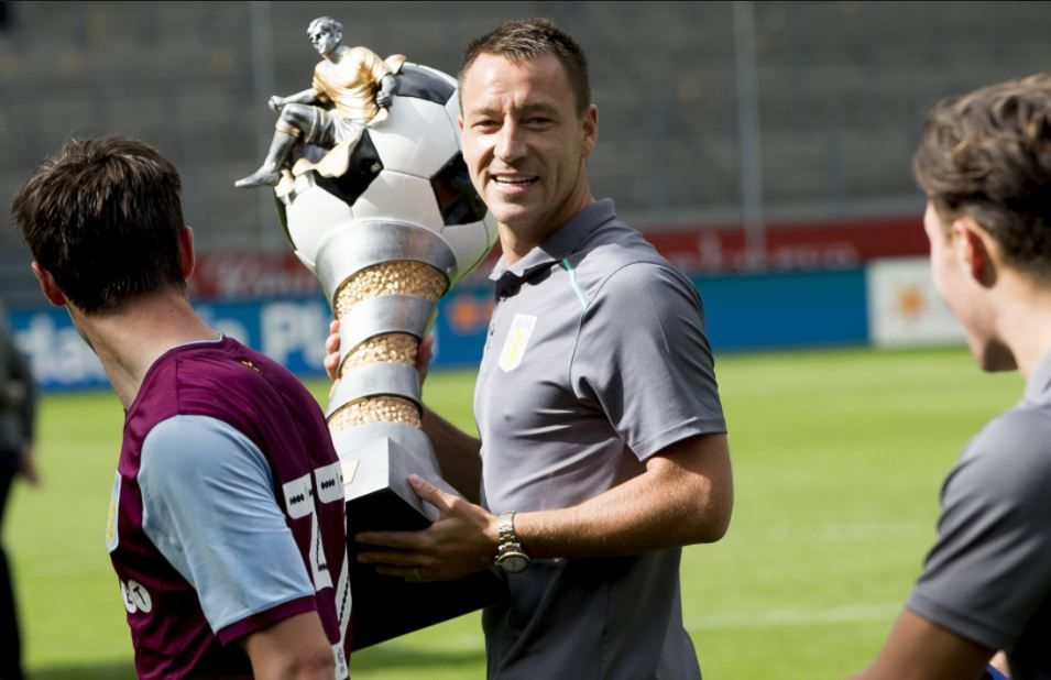 John Terry carries the Cup of Traditions won by Aston Villa in preseason