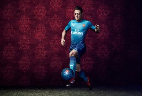 Arsenal's Mesut Ozil models the club's new blue away kit