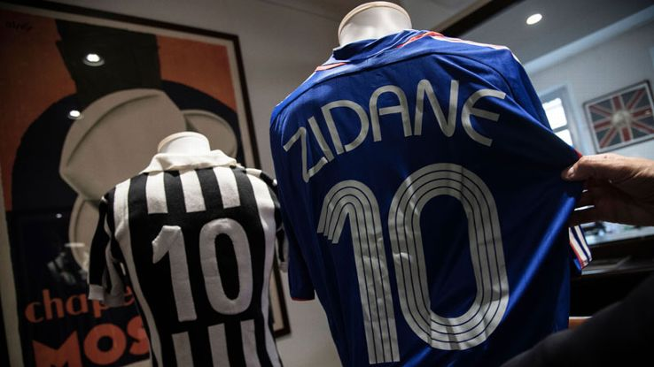 A man displays a French national football team jersey worn by Zinedine Zidane