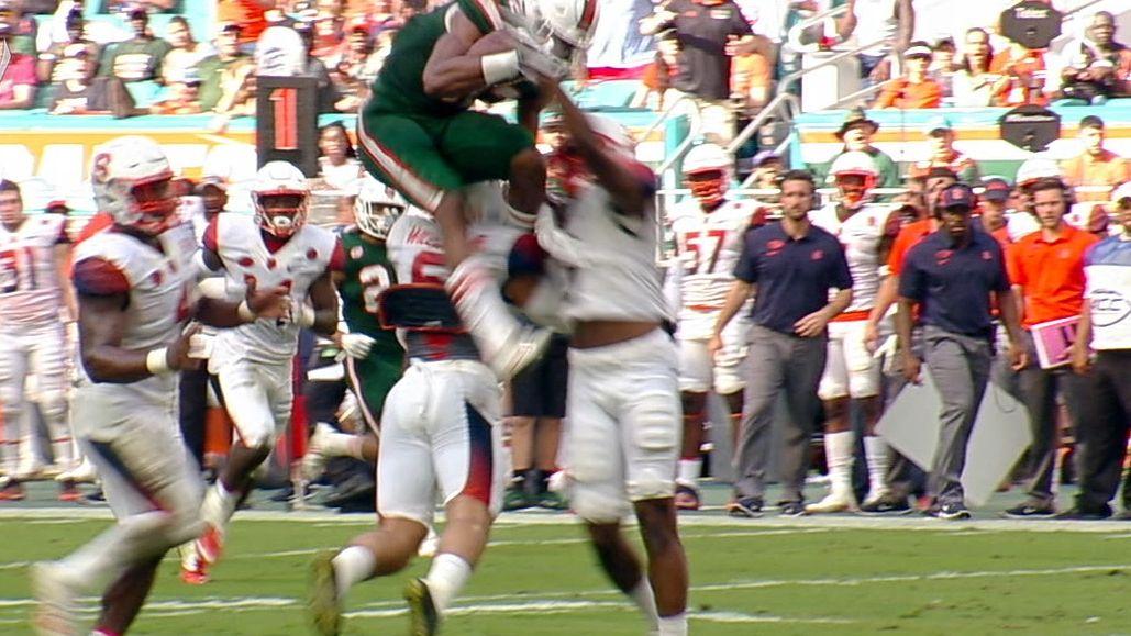 Miami's Richards hurdles over defender