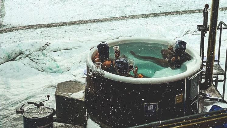 Danish fans watch team play snowbound match from pitchside hot tub