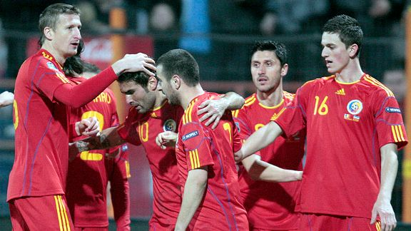 Adrian Mutu is mobbed after scoring one of his two in Romania's win over Luxembourg.