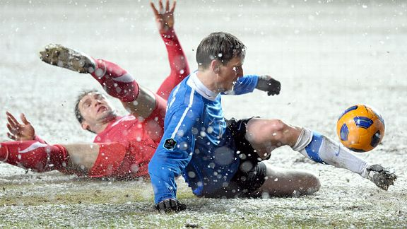 Estonia's Raio Piiroja, right, and Serbia's Branislav Ivanovic struggle for the ball in the snow as the teams draw 1-1.