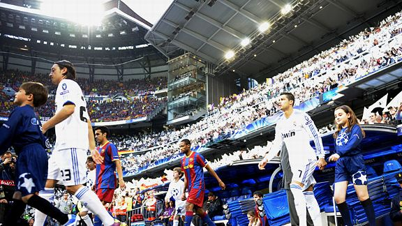 Real Madrid and Barcelona players walk out into the cauldron  of the Bernabeu.