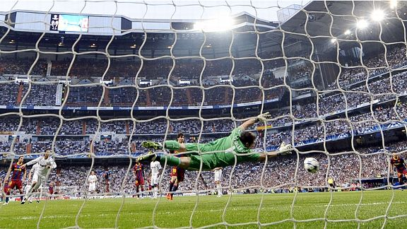 Iker Casillas is forced to dive to guide David Villa's shot wide of the upright.