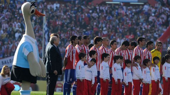 Suri, the Copa America mascot, lines up next to the Paraguay players
