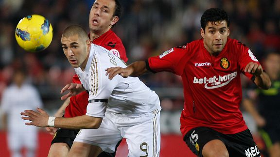Real Madrid's Karim Benzema duels for the ball with Mallorca's Pablo Caceres