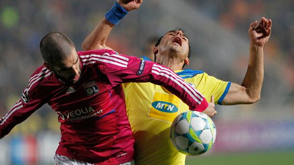 Savvas Poursaitides of Apoel Nicosia fights for the ball with Lisandro of Lyon