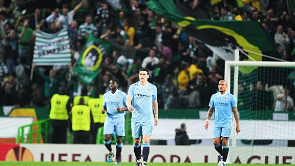 Man City players trudge back to the centre circle as Sporting players celebrate Xandao's goal.