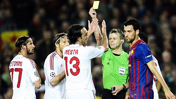 Alessandro Nesta gets a yellow card after tugging back Sergio Busquets for Barcelona's second penalty.