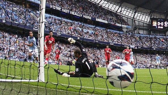 Carlos Tevez slots the ball past Kelvin Davis to give Man City the lead.