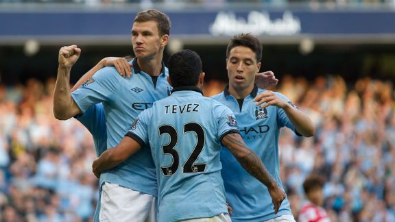 Edin Dzeko celebrates with his team-mates after putting Manchester City into a 2-1 lead
