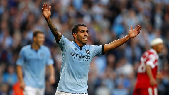 Carlos Tevez celebrates after wrapping up the scoring against QPR