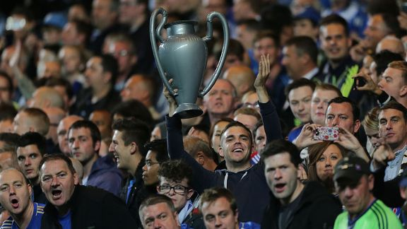 A Chelsea fan celebrates with an inflatable Champions League trophy for the Blues' first match in defence of their trophy