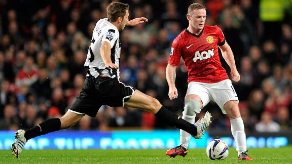 Manchester United's Wayne Rooney, right, is tackled by Newcastle's United's Dan Gosling