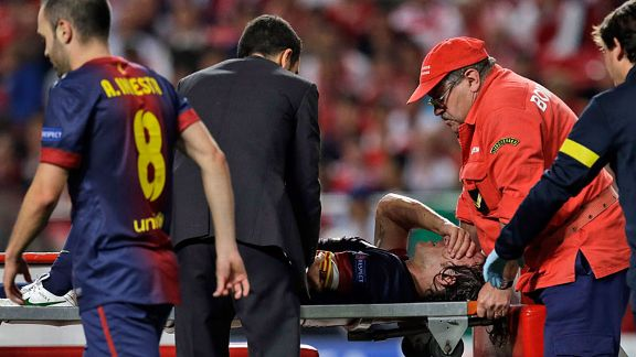 Carles Puyol has his arm held by a team doctor after injuring it in a fall against Benfica