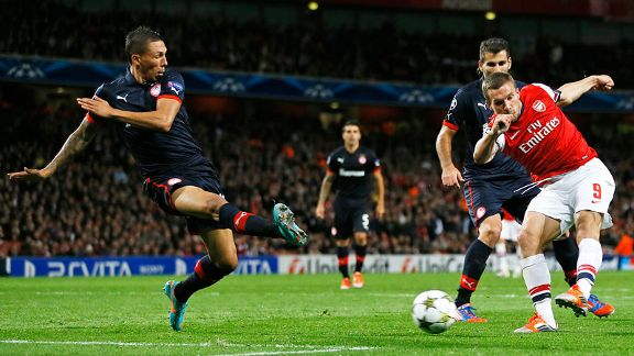 Arsenal's Lukas Podolski, right, scores his sides second goal