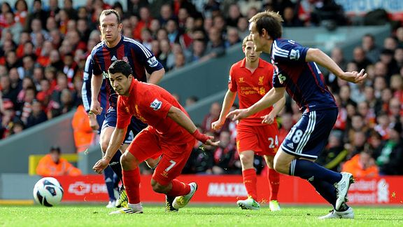 Luis Suarez of Liverpool bursts through the Stoke players