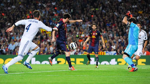 Lionel Messi of Barcelona scores his team's first goal past Iker Casillas