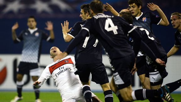 Dinamo Zagreb players protest their innocence as PSG's Jeremy Menez claims a foul
