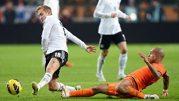 Lewis Holtby is tackled by Nigel de Jong in Germany's friendly with Netherlands