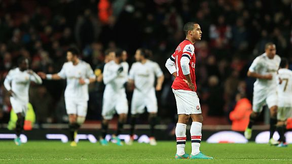 Theo Walcott is a lonely figure as Swansea celebrate one of Michu's two goals