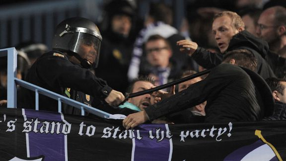 A riot policeman uses his baton on an Anderlecht fan during the Belgian side's 2-2 draw at Malaga