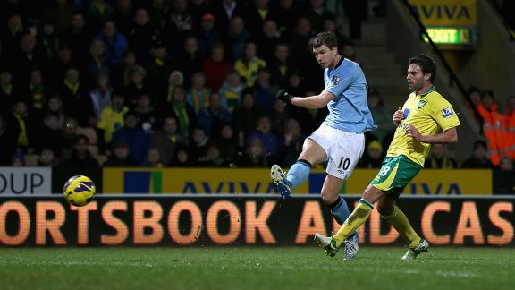 Edin Dzeko shoots on goal as Manchester City net their fourth at Norwich