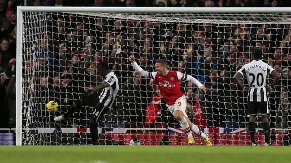 Lukas Podolski celebrates after putting Arsenal 3-2 ahead with a close-range finish