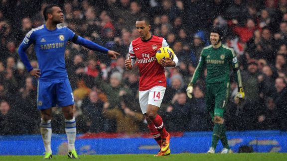Theo Walcott returns to the centre circle after scoring against Chelsea