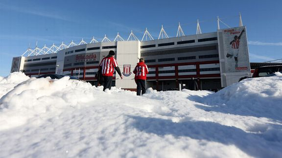 Stoke City fans make their way to the Britannia Stadium in the snow