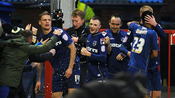 Matt Smith celebrates with his team-mates after putting Oldham into a 2-1 lead