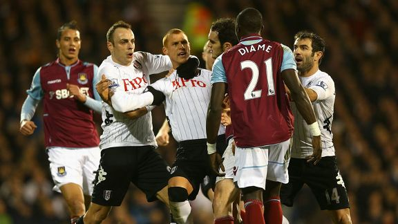 Steve Sidwell is held back by his Fulham team-mates as he squares up to West Ham's Mohamed Diame