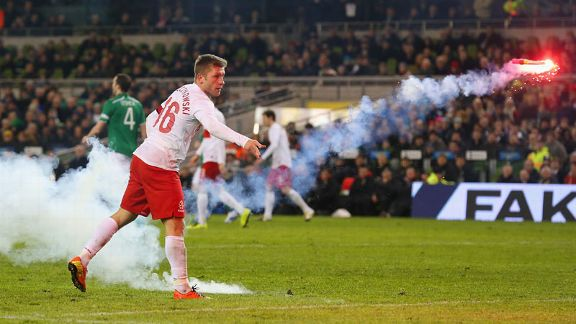 Jakub Blaszczykowski clears a flare from the field during Poland's 2-0 defeat to Ireland
