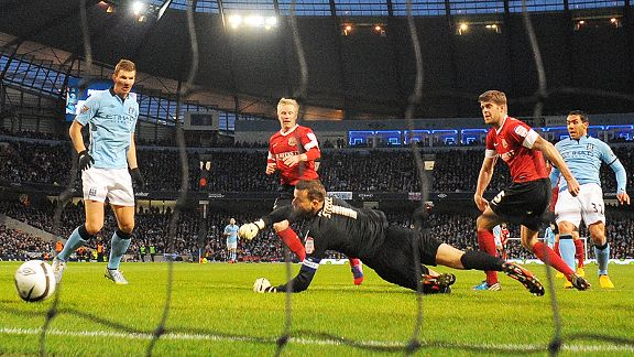 Carlos Tevez scores the second of his three goals in Man City's rout of Barnsley in the FA Cup